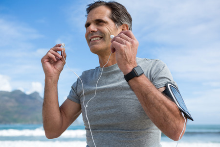 Smiling man listening to music on headphones on beach