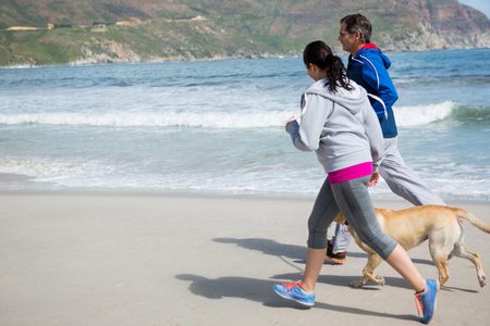Couple jogging with pet dog on beach Stock Photo