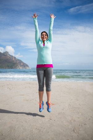 Excited woman jumping on beach during winter