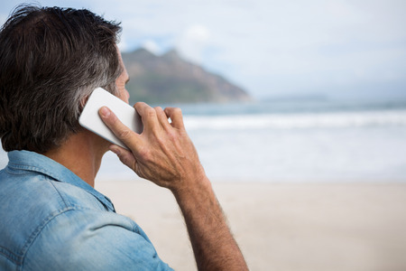 Man talking on mobile phone on beach during winter