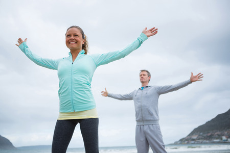 Couple performing stretching exercise on beach Stock Photo