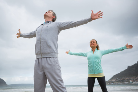 Couple standing with arms outstretched on beach during winter
