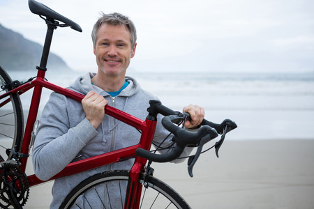 Happy man carrying bicycle on beach during winter