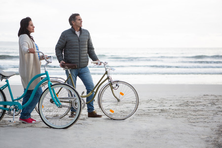 Couple standing with bicycle on beach during winter