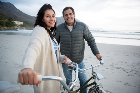 Portrait of couple standing with bicycle on beach during winter