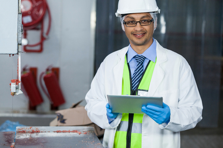 Portrait of technician holding digital tablet at meat factory