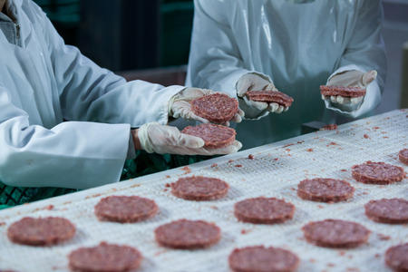 Butchers processing hamburger patty at meat factory