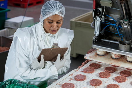 Female butcher processing hamburger patty at meat factory