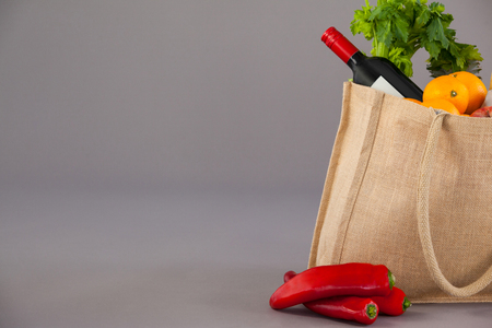 Wine bottle and vegetables in grocery bag against grey background