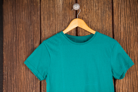 wood panelling: Turquoise t-shirt on hanger on wood panelling