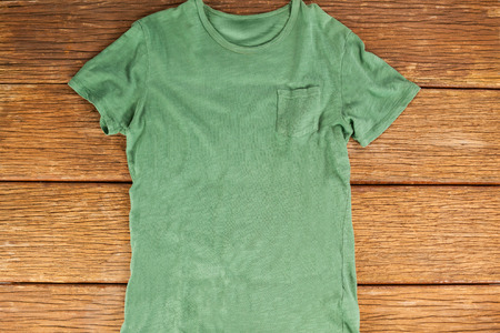 wood panelling: Green pocket t-shirt on wood panelling