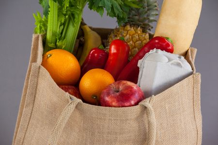 Close-up of vegetables and fruits in grocery bag against grey background