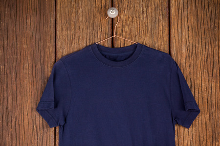 navy blue: Navy blue t-shirt on hanger on wood panelling