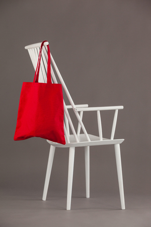 Red bag hanging on a white chair against grey background