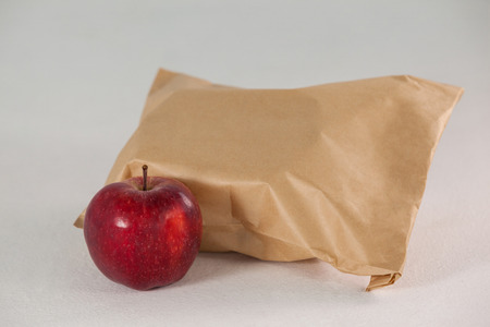 apple paper bag: Brown paper lunch bag with red apple against grey background