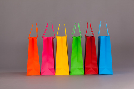 overspending: Colorful shopping bags against grey background Stock Photo