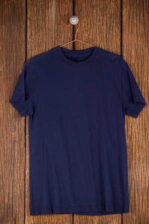 wood panelling: Navy blue t-shirt on hanger on wood panelling