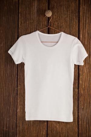wood panelling: White t-shirt on hanger on wood panelling