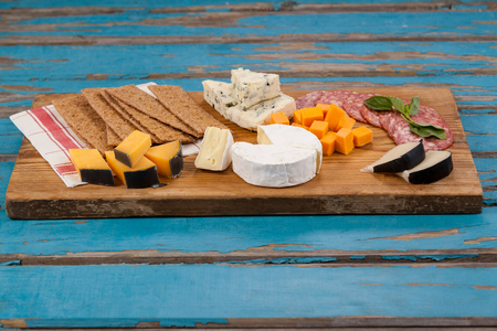 Close-up of various cheese with ham and crispy biscuits on chopping board
