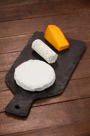 Close-up of different types of cheese on chopping board