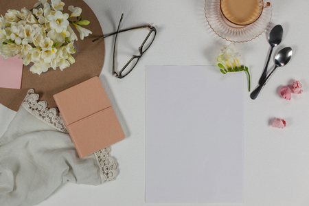 Cup of tea, spoons, spectacles, diary, cloth, blank page, paper balls and flowers on white background Stock Photo