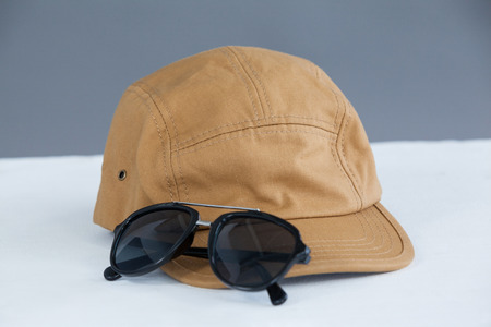 Close-up of brown cap with sunglasses against grey background