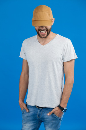Cheerful man in cap against blue background