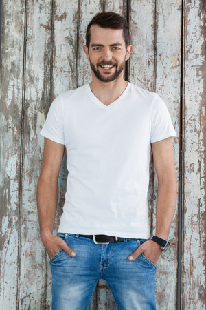 Portrait of handsome man in white t-shirt and blue jeans standing against wooden background