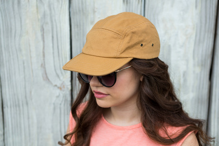 Woman in brown cap and sunglasses against wooden background