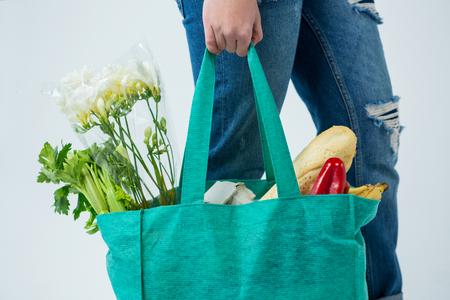 白い背景に、食料品の袋を運ぶ女性の中間セクション
