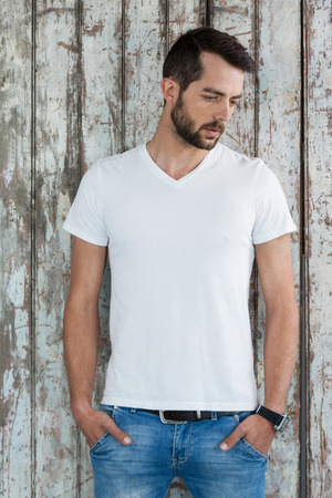 Handsome man in white t-shirt and blue jeans standing against wooden background