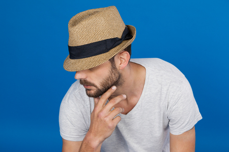 Man in fedora hat against blue background Stock Photo