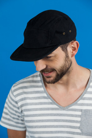 Close-up of man in cap against blue background