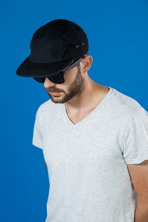 Man in cap and sunglasses against blue background
