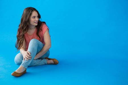Smiling woman sitting against blue background Stock Photo