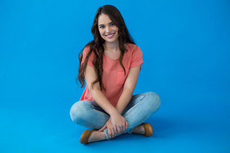 Portrait of a beautiful woman sitting against blue background Stock Photo