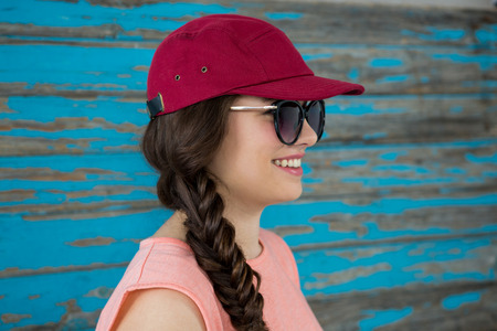 Smiling woman in red cap and sunglasses against wooden background Stock Photo