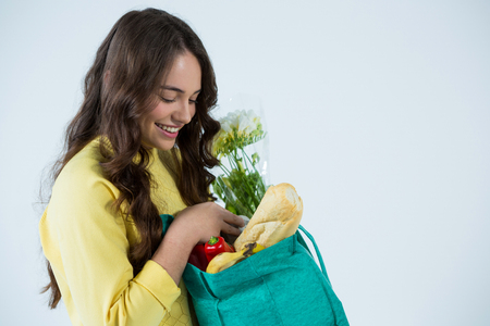 Smiling beautiful woman looking at grocery bag against white background