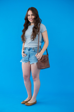 shoulder bag: Portrait of a beautiful woman in grey t-shirt with shoulder bag against blue background Stock Photo