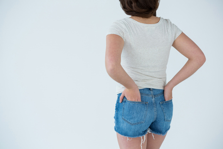 Rear view of a woman in white t-shirt and hot pants against white background Stock Photo