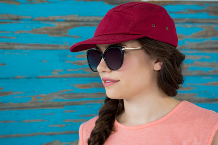 Woman in red cap and sunglasses against wooden background Stock Photo