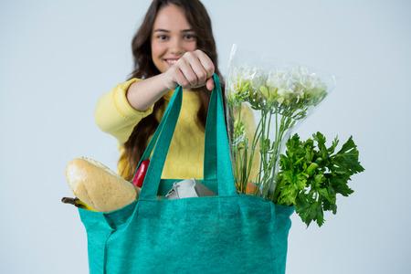 Portret van de mooie zak van de vrouwen dragende kruidenierswinkel tegen witte achtergrond
