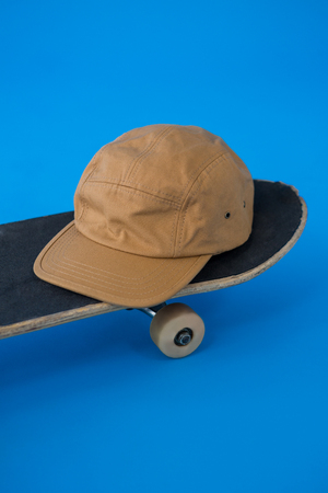 Brown cap on skateboard against blue background