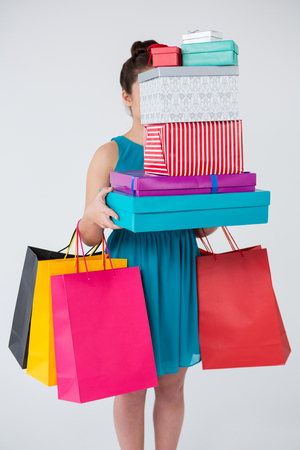 Woman carrying stack of gift boxes and shopping bags against white background