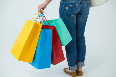 Low section of a woman carrying colorful shopping bags against white background Stock Photo