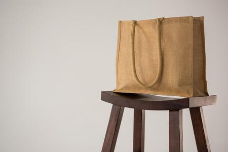 Jute bag on wooden stool against white background Stock Photo