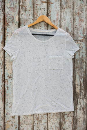 wood panelling: White t-shirt with pocket on hanger against wood panelling