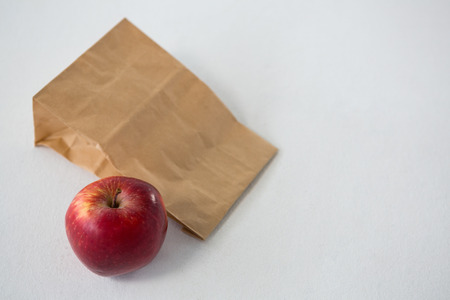 apple paper bag: Brown paper parcel bag with red apple against white background