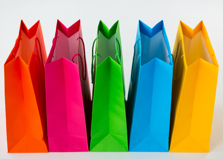 overspending: Close-up of colorful shopping bags against white background