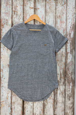 wood panelling: Grey t-shirt with pocket on hanger against wood panelling Stock Photo